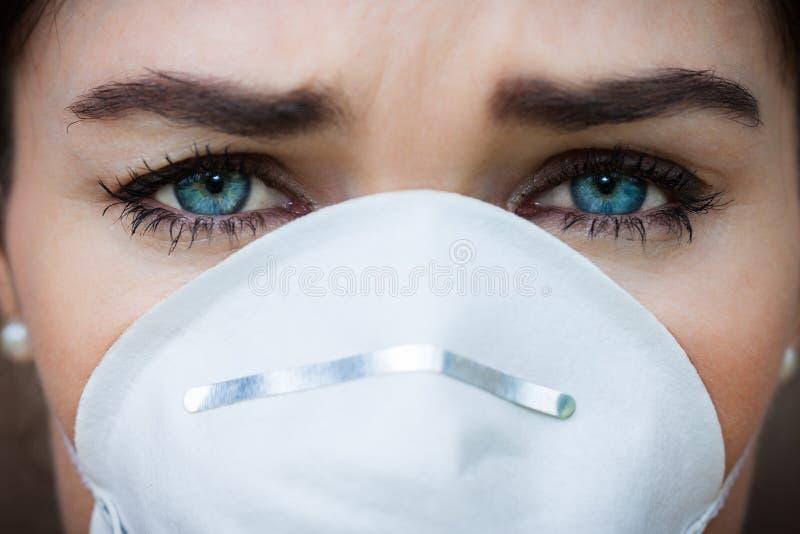Nahaufnahmeporträtfrau, die eine Gesichtsmaske trägt lizenzfreie stockfotografie