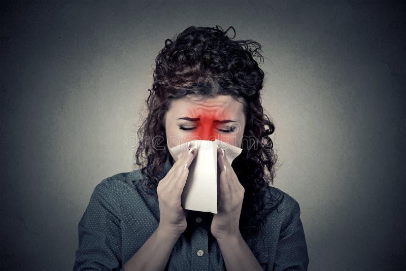 Nahaufnahmeporträtfrau, die in einem Gewebe durchbrennt ihr flüssiges kein niest stockbild
