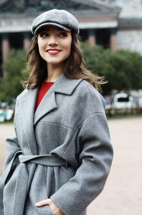 Nahaufnahmeportr?t der jungen Frau in der eleganten grauen Mantelstellung auf der Stra?e am Herbsttag stockfotos