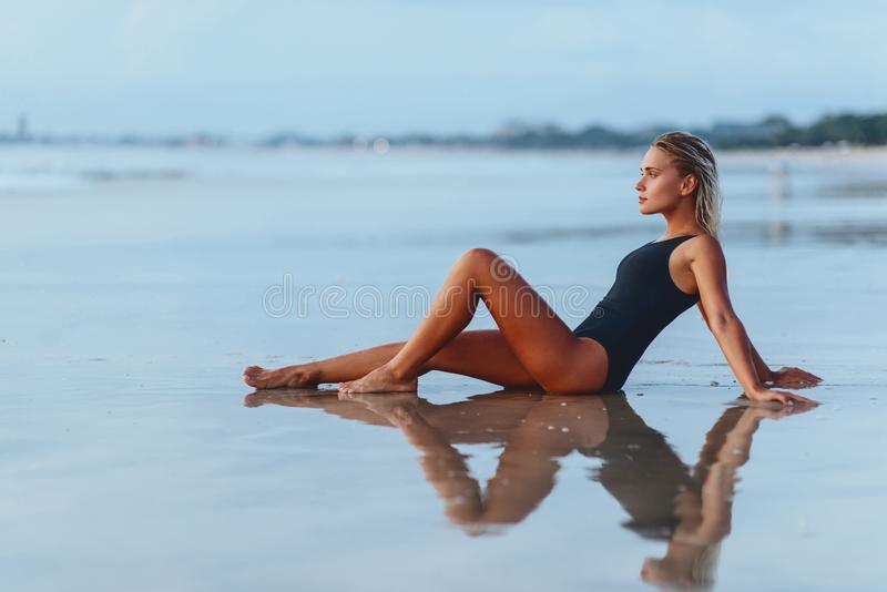 Nahaufnahmeportr?t des attraktiven blonden M?dchens mit dem langen Haar, das auf Strand aufwirft stockbild
