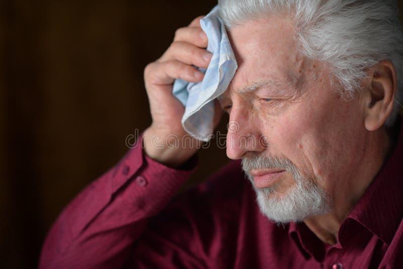 Nahaufnahmeportr?t des traurigen ?lteren Mannes mit Kopfschmerzen stockfotos