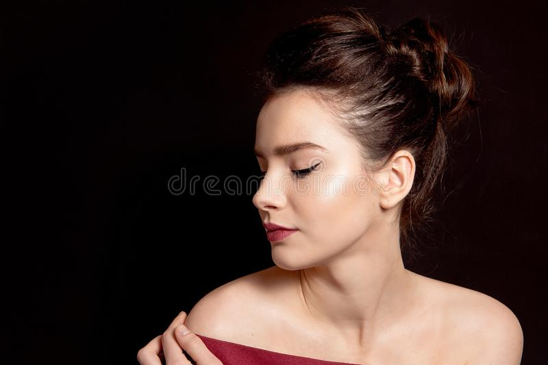 Nahaufnahmeportr?t einer Frau mit klassischem Make-up mit einem schwarzen Pfeil und einer blo?en Lippe ?ber ihren Schultern auf e stockbild