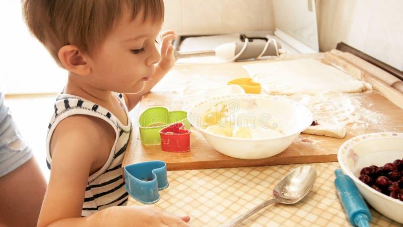 Nahaufnahmeportr?t von 3 Jahren Kleinkindjungen-Stellung auf K?che und kochen Teig Kinderbacken und Herstellungsfr?hst?ck stockfoto