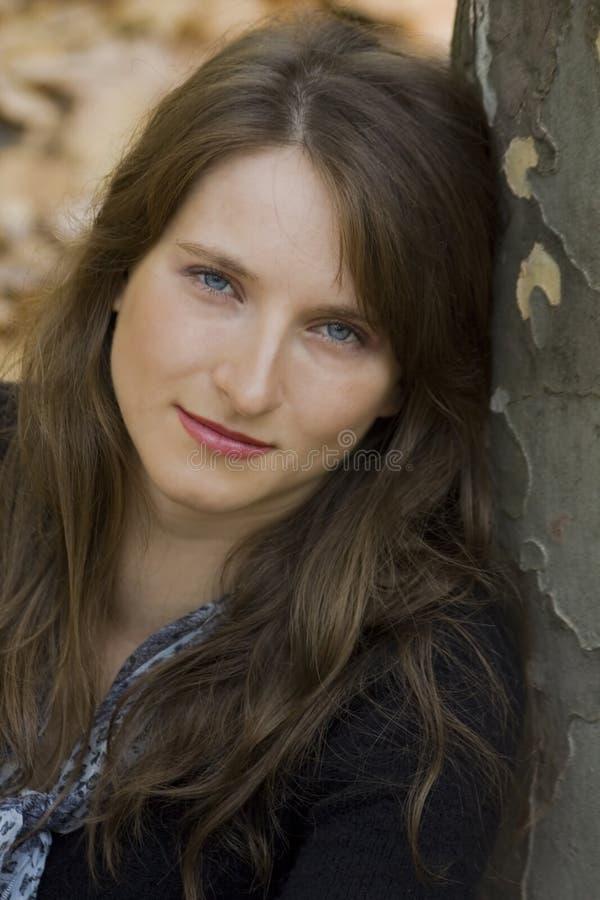 Nahaufnahmeportrait der jungen Frau nahe dem Baum lizenzfreies stockfoto