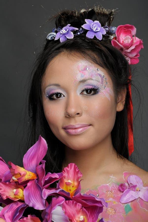 Nahaufnahmeportrait des asiatischen Mädchens mit Blumen lizenzfreie stockbilder