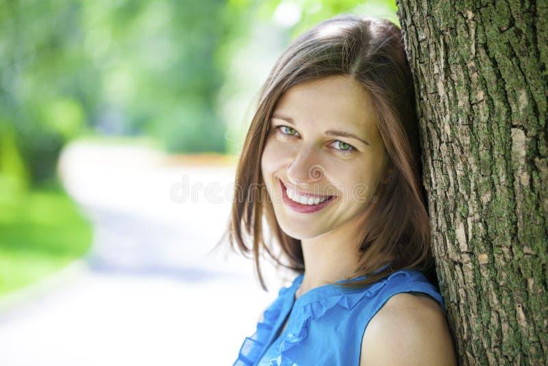 Nahaufnahmeportrait eines glücklichen Lächelns der jungen Frau stockfotografie