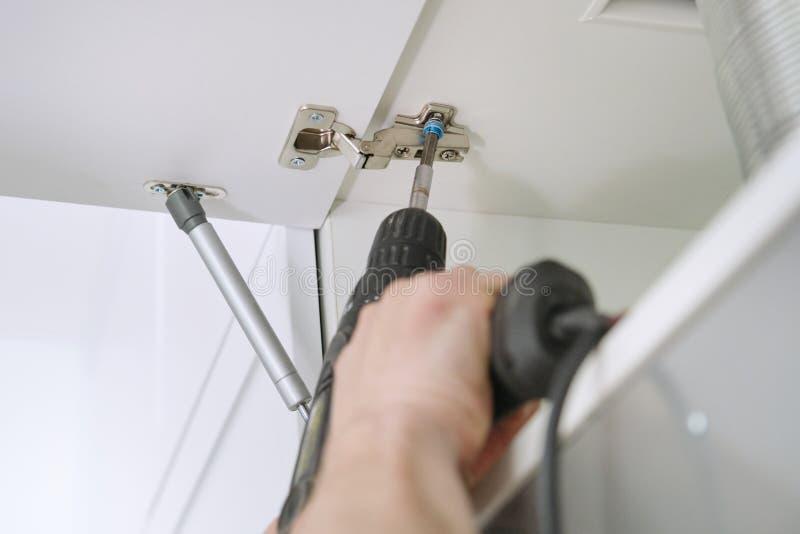 Nahaufnahmeprozeß des Zusammenbauens von Küchenmöbeln, Hände der männlichen Arbeitskraft mit Berufswerkzeugen lizenzfreies stockbild