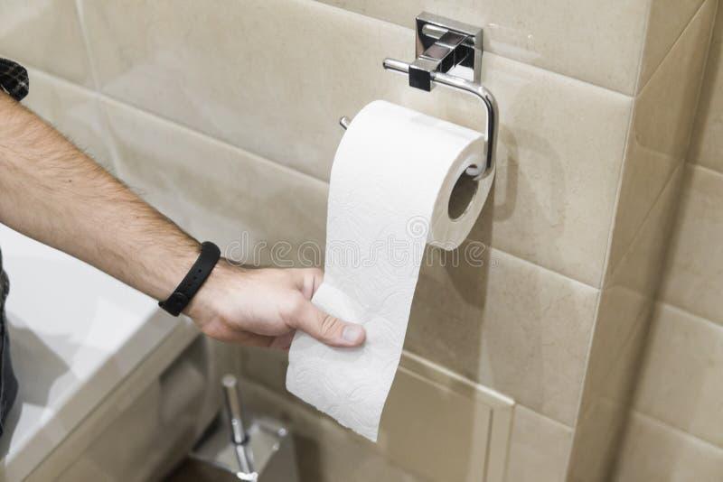 Nahaufnahmerollentoilettenpapier in der Toilette mit Handdem ziehen stockbild