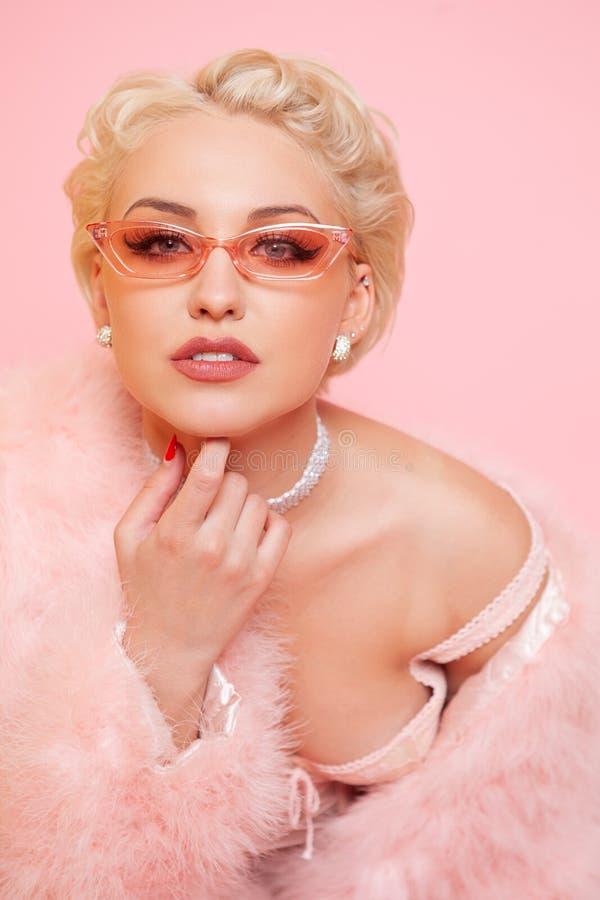 Nahaufnahmeschönheitsporträt der jungen Frau mit den rosa Lippen, den langen falschen Wimpern, Pelzmantel und Schmuck Rote Manikü stockfoto