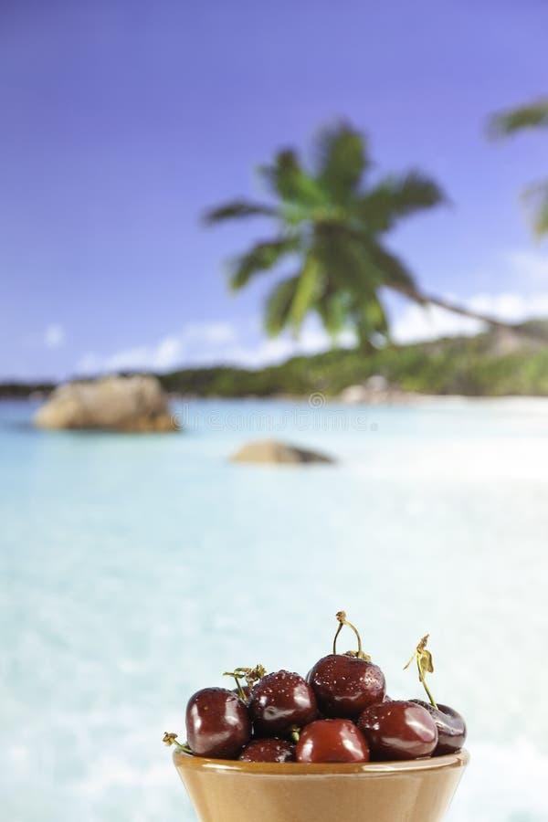 Nahaufnahmeschüssel rote Kirschen auf dem Strand stockfoto
