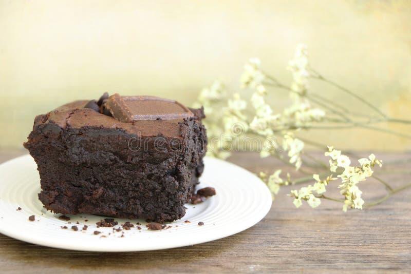 Nahaufnahmeschokoladenschokoladenkuchen in der weißen Platte auf Holztisch mit schöner Blume lizenzfreie stockbilder