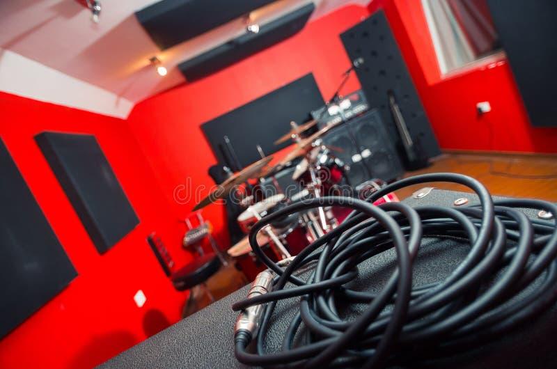 Nahaufnahmeschwarze Audiostandardkabel rollten in Bündel, in Studiohauptschreibtisch und in Einrichtung im Hintergrund stockfotografie