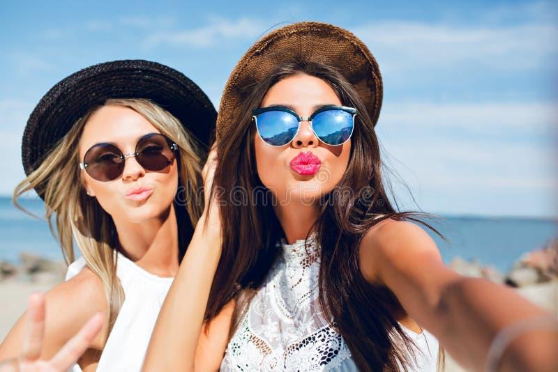 Nahaufnahmeselfieporträt attraktiven Brunette zwei und der blonden Mädchen mit dem langen Haar, das auf dem Strand steht Sie Abnu stockbilder