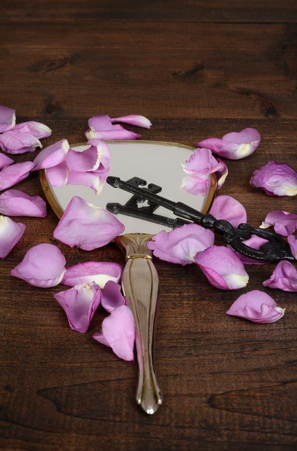 Nahaufnahmespiegel mit den rosa rosafarbenen Blumenblättern und einem Schlüssel lizenzfreie stockfotos
