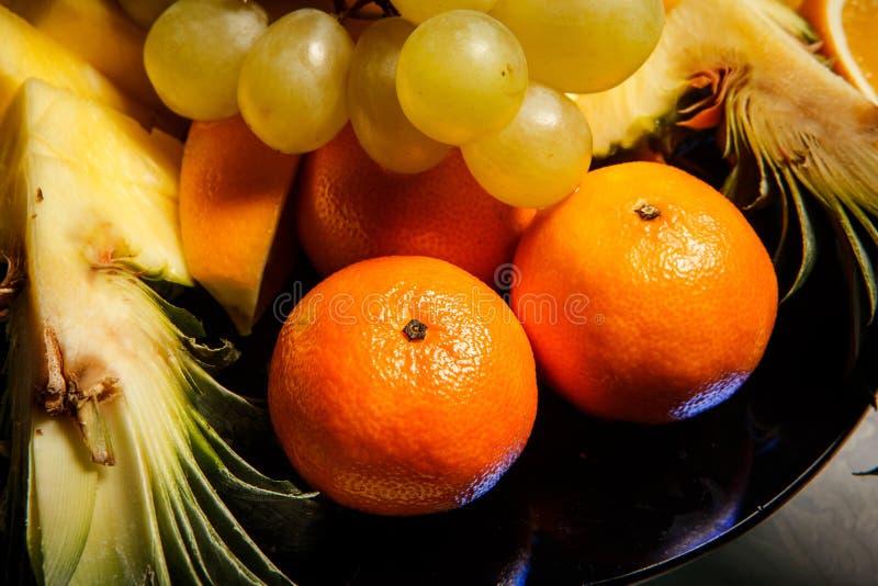 Nahaufnahmetangerinen und sortierte tropische Früchte auf großer Platte lizenzfreie stockfotos