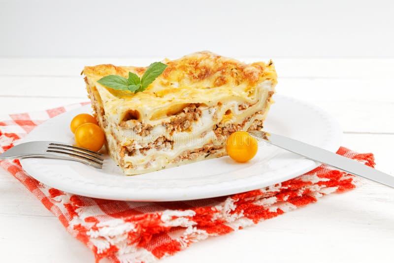 Nahaufnahmeteil selbst gemachte Lasagne auf weißem Holztisch lizenzfreies stockfoto