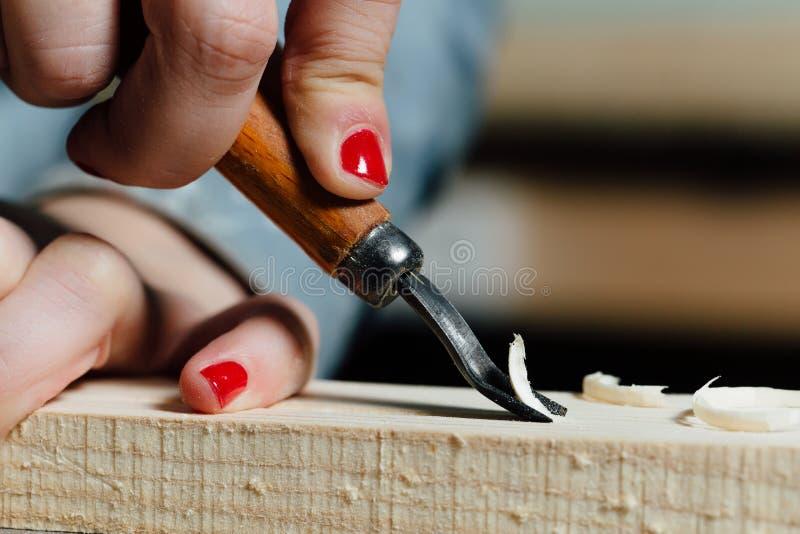 Nahaufnahmetischlerfrau ` s Hand mit einer roten Maniküre behandelt den Baum, schneidet die Schnitzel stockfotos