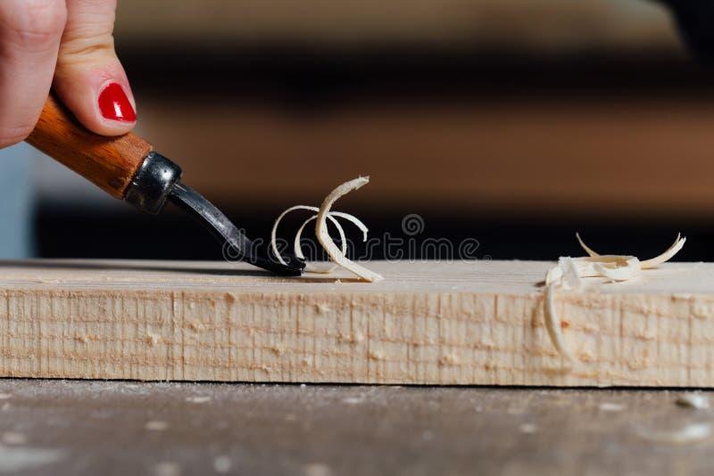 Nahaufnahmetischlerfrau ` s Hand mit einer roten Maniküre behandelt den Baum, schneidet die Schnitzel lizenzfreies stockfoto