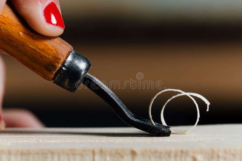 Nahaufnahmetischlerfrau ` s Hand mit einer roten Maniküre behandelt den Baum, schneidet die Schnitzel lizenzfreie stockbilder