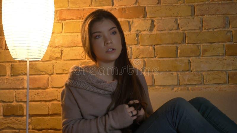 Nahaufnahmetrieb der jungen netten kaukasischen Frau, die eine Fernsehshow fasziniert wird in einer gemütlichen Wohnung aufpasst stockfotos