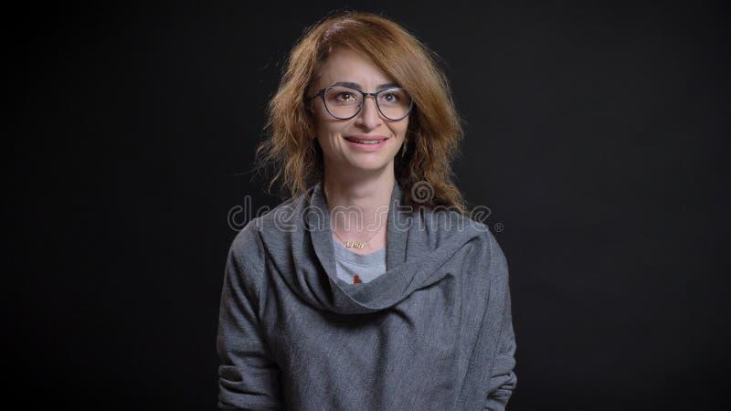 Nahaufnahmetrieb der Mitte gealtert, die behaarte kaukasische Frau in den Gläsern zu lesen nett lächelnd beim mit vorwärts schaue lizenzfreie stockfotografie