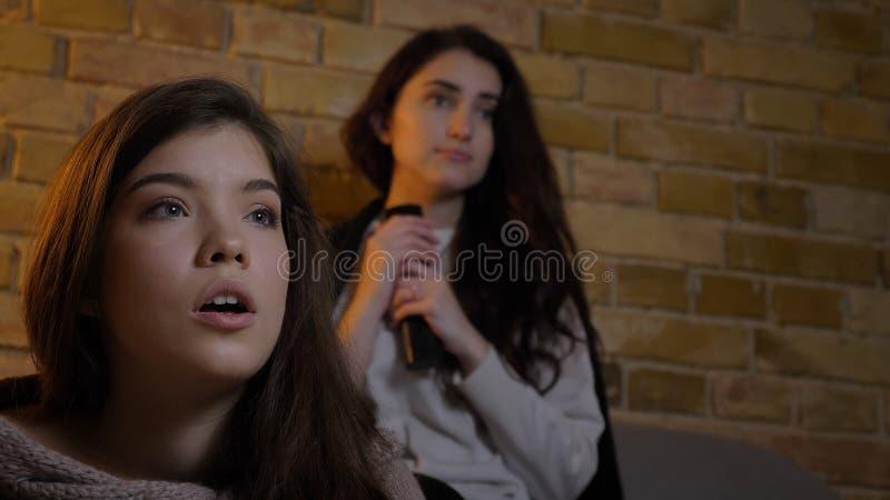 Nahaufnahmetrieb von zwei jungen netten Mädchen, die Fernsehzusammen witn aufpassen, entsetzte Gesichtsausdrücke beim Stillstehen lizenzfreies stockfoto