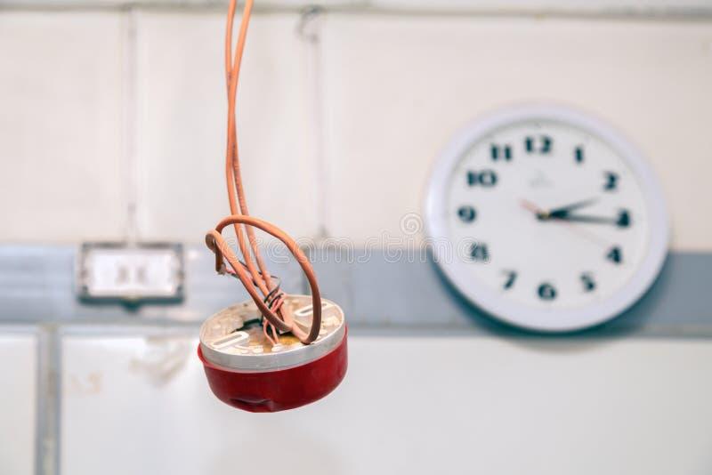 Nahaufnahmeuhr und Installation und Reparatur der elektrischen Leitung, Rauchmelder, Brandmeldeanlage vor der Installierung Konze lizenzfreie stockbilder