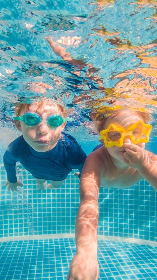 Nahaufnahmeunterwasserporträt des zwei netten lächelnden Kindvertikalen FORMATS für bewegliche Geschichte Instagram oder Geschich stockfotografie