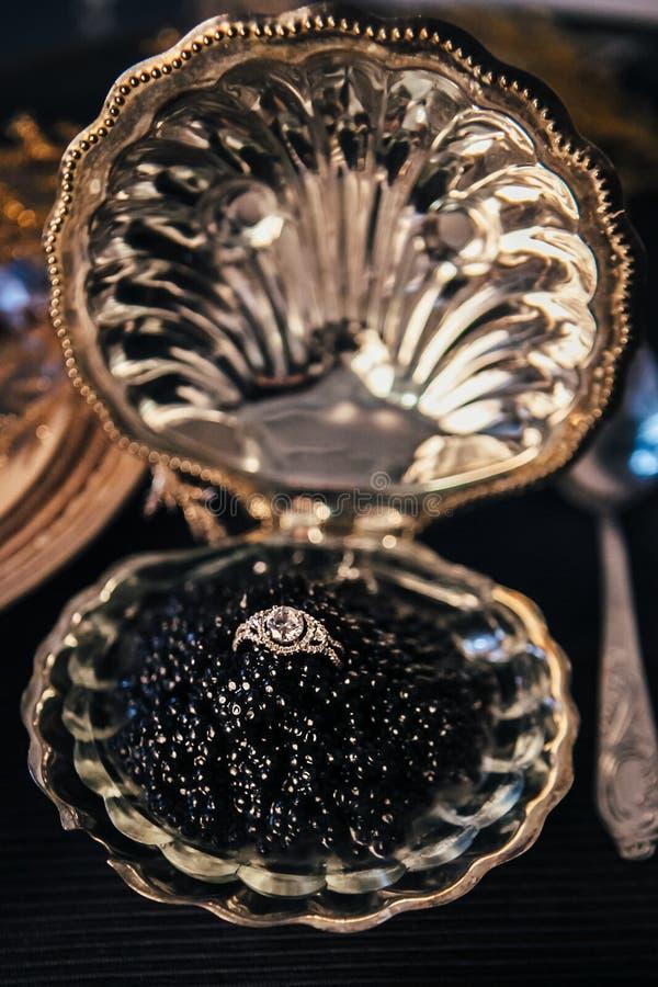 NahaufnahmeVerlobungsring mit einem enormen Diamanten in einer Schüssel mit schwarzem Kaviar, eleganter Dekor für eine Heiratszer lizenzfreies stockfoto