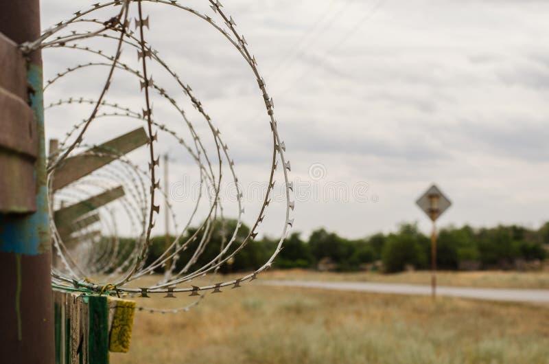 Nahaufnahmezaun mit Stacheldraht gegen eine ländliche Landschaft lizenzfreie stockbilder
