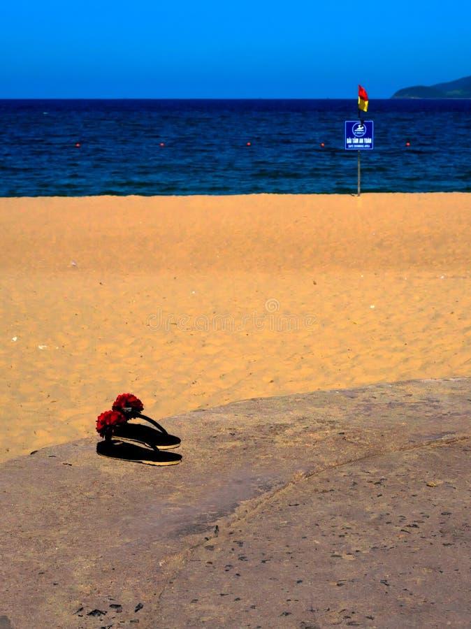 Nahe Ansicht über Flipflops durch den Strand Vietnam Nha Trang lizenzfreie stockfotos