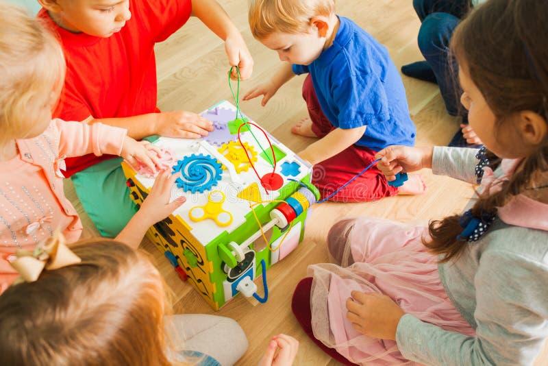 Nahe Ansicht des beschäftigten Würfelspielzeugs mit den Kindern, die herum sitzen lizenzfreie stockfotografie