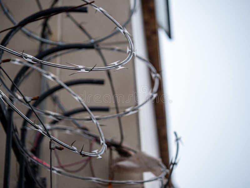 Nahe Ansicht des Stacheldrahtrasiermesserdrahtes auf Zaun außerhalb eines Gebäudes in der Überwendlingsnaht stockfoto