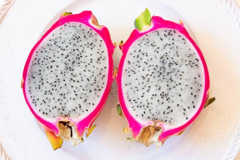 Nahe Ansicht von zwei schnitt die weiße Drachefrucht, die rosa Rinde und schwarzen die Samen zeigt, zentriert auf Platte stockbild