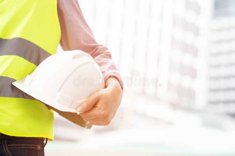 Nahe ehrliche Ansicht der Technik des männlichen Bauarbeiters, der weißen Sturzhelm der Sicherheit hält stockfotografie