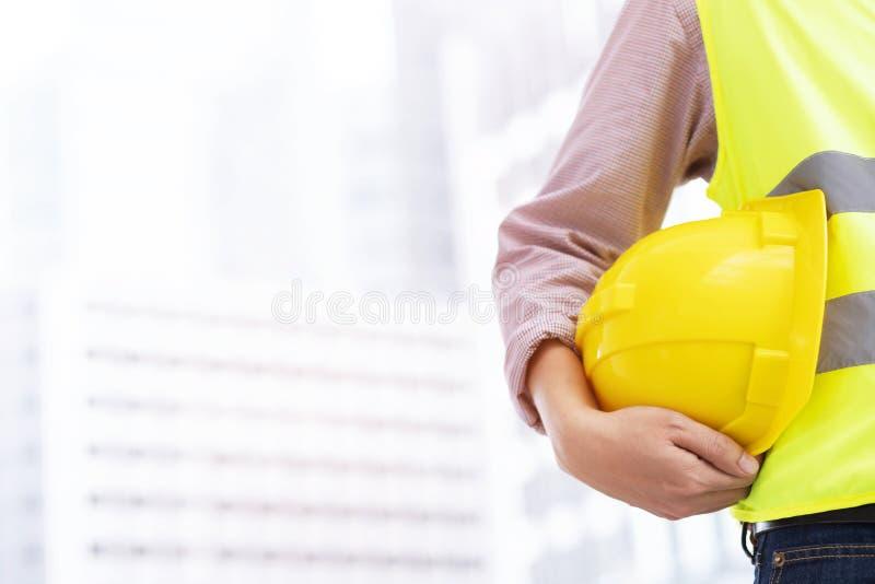 Nahe ehrliche Ansicht der Technik des männlichen Bauarbeiterstands, der gelben Sturzhelm der Sicherheit hält stockfotos