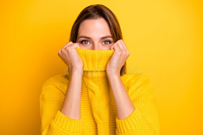 Nahe Foto von positivem fröhlichen Mädchen verbergen ihre Gesichter Lippen fühlen sich schüchtern auf kalte Temperatur Wetter fre lizenzfreies stockbild