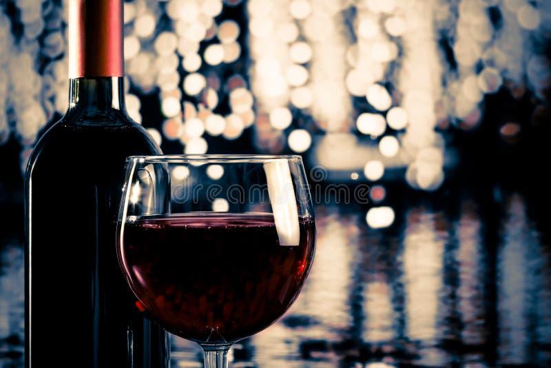 Nahe Glasflasche des Rotweins mit hellem bokeh stockfotografie