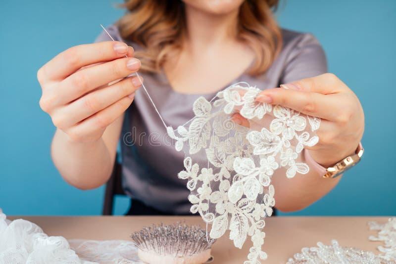 Nahe Hände der Schneider-Schneider-Schneider-Designer Hochzeitskleid Nähbekleidung Nähperlen auf einem blauen Hintergrund in eine stockbild