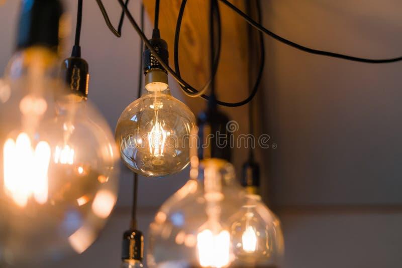 Nahe hohe Ansicht der dekorativen hellen Lampenbirne der Weinlese, die zuhause auf die Decke glüht Transparente Lampen, die mit w stockfoto