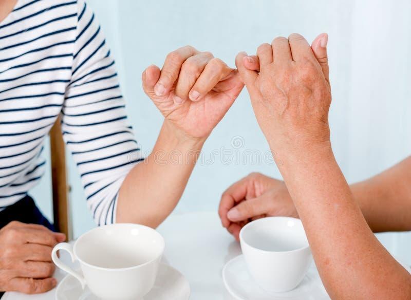 Nahe hohe Ansicht des älteren Frauenhakens jede andere kleiner Finger zum anderen mit dem Lächeln vor Balkon im Haus stockbild