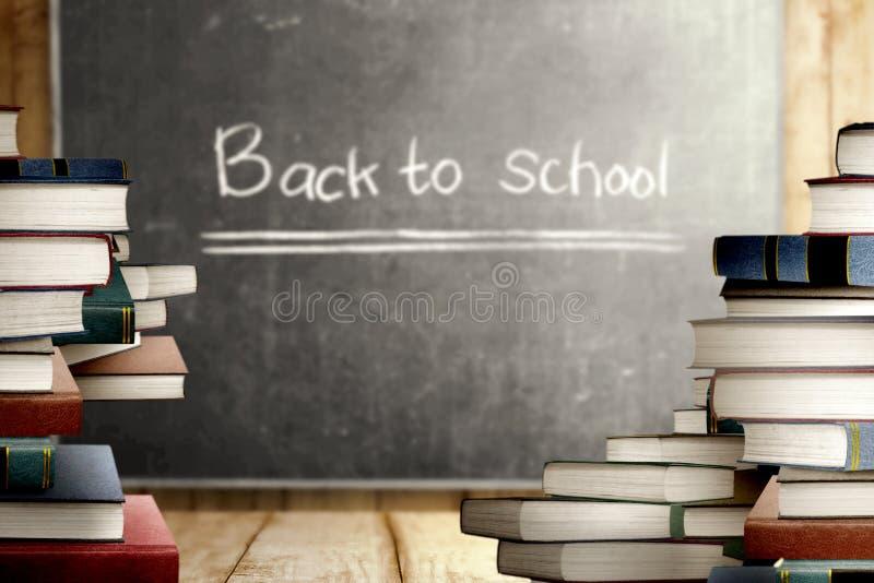 Nahe hohe Ansicht des Stapels der Bücher auf Holztisch und Tafel mit zurück zu Schulmitteilung lizenzfreie stockfotos