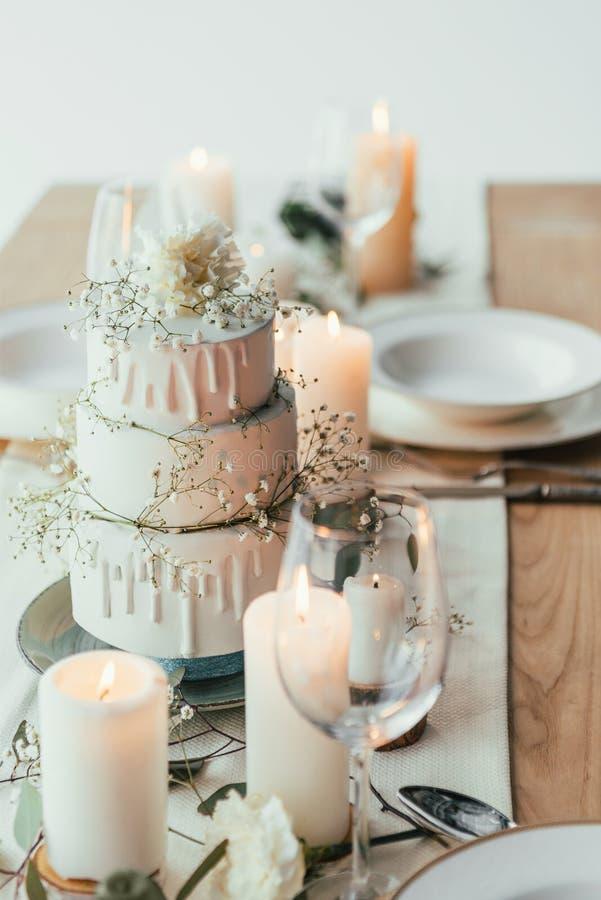 nahe hohe Ansicht des stilvollen Gedecks mit Kerzen und Hochzeitstorte lizenzfreie stockbilder