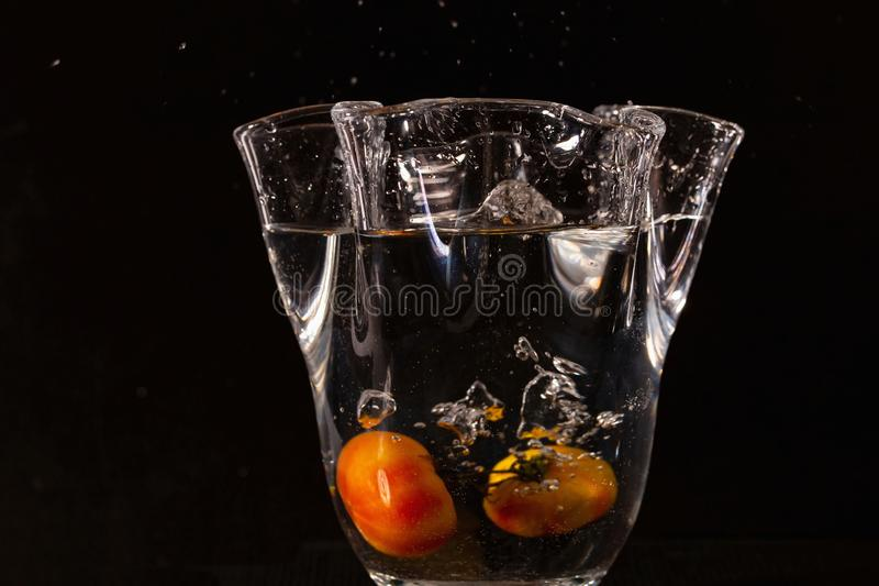 Nahe hohe Ansicht des Vase mit Spritzwasser und gelben Früchten in ihm auf schwarzem Hintergrund stockfotografie