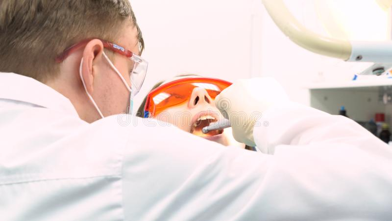Nahe hohe Ansicht des Zahnarztes in den Latexhandschuhen Frau mit geöffnetem Mund, Zahnpflegekonzept überprüfend media Zurück von lizenzfreie stockfotografie