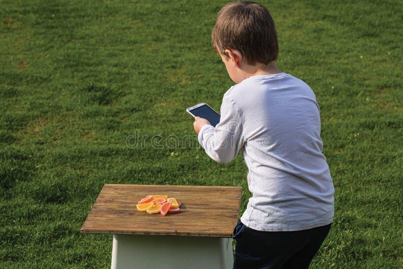 Nahe hohe Ansicht eines Jungen, der Foto von Süßigkeiten auf seinem Mobile macht lizenzfreies stockbild