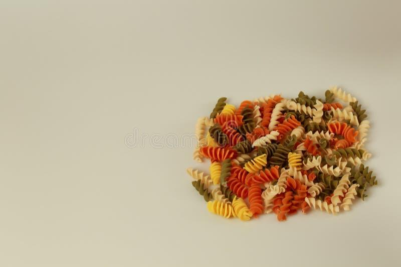 Nahe hohe Ansicht von ganzen Kornteigwaren der bunten Spirale Gesunder Nahrungsmittelhintergrund lizenzfreie stockbilder