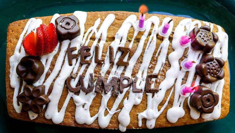 Nahe hohe Ansicht von oben eines selbst gemachten alles- Gute zum Geburtstagkuchens mit Wörtern auf spanisch gemacht von der Scho lizenzfreies stockfoto
