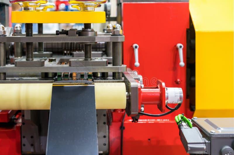 Nahe hohe Blechtafel auf Rolle und Form sterben während der Zufuhr zur automatischen Presse der Spitzentechnologie und der Präzis stockbild