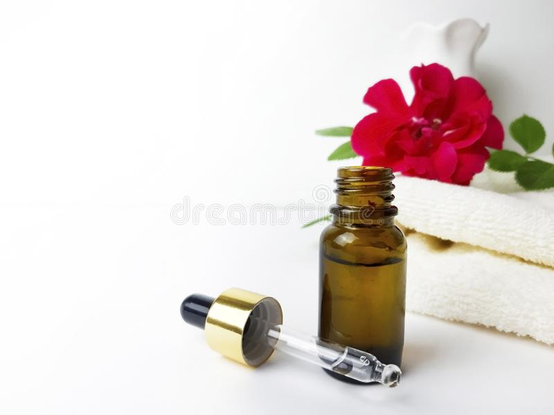 Nahe hohe Flasche rosafarbenes ätherisches Öl für kosmetische, abwechselnde Medizin und Parfümerie lizenzfreie stockfotos